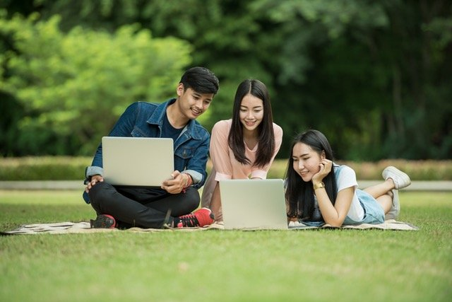 Three young people using laptops on grass